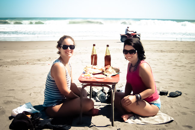 two girls eating lunch on the beach