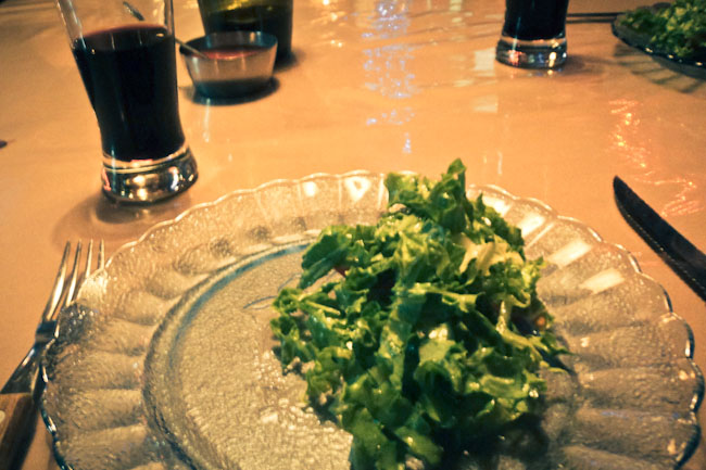 salad on a plate with red wine