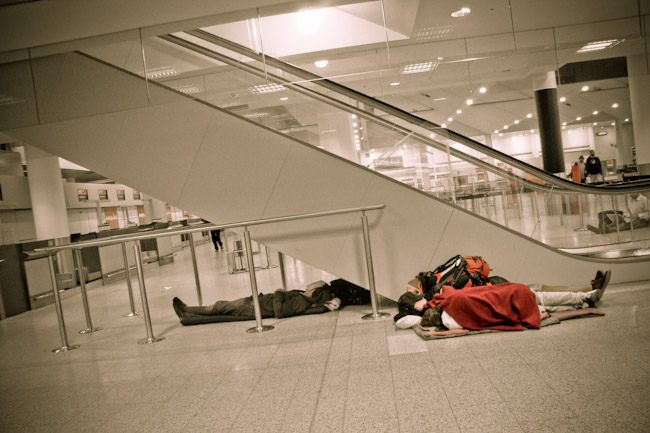 sleeping in airport by escalator