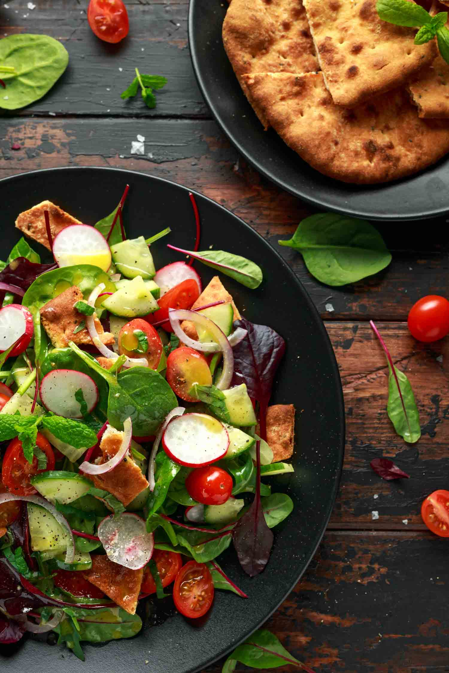 Traditional food in Jordan fattoush salad on a plate with pita croutons, cucumber, tomato, red onion, vegetables mix and herbs
