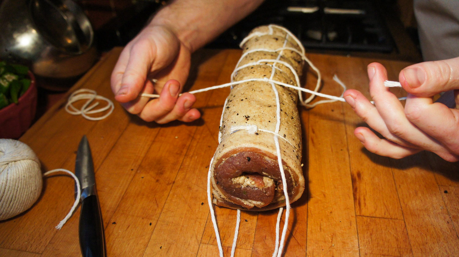 Tying a butcher knot on a roll of pancetta