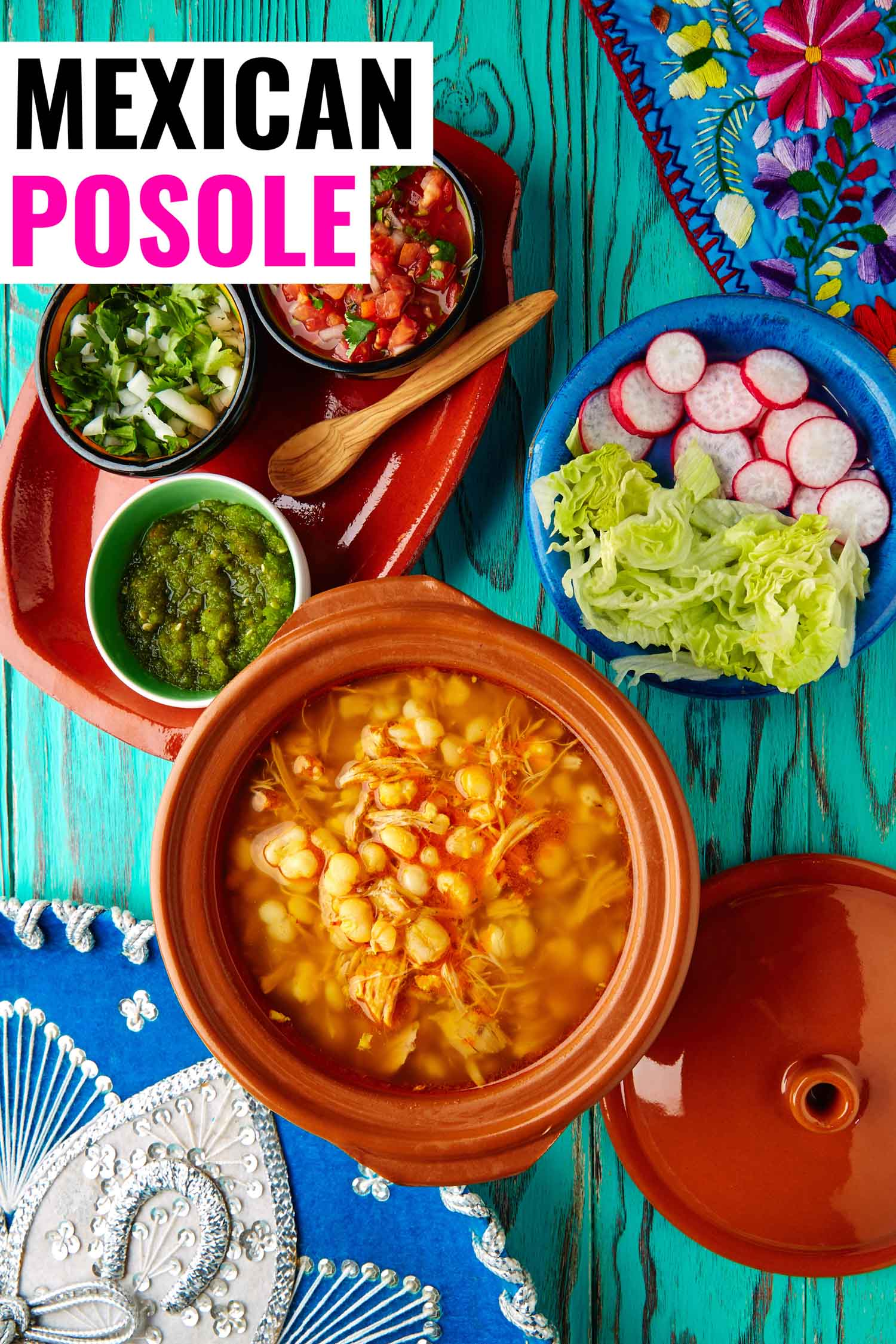Mexican stew called pozole on a bright background with all of the garnishes like radish, lettuce and salsa