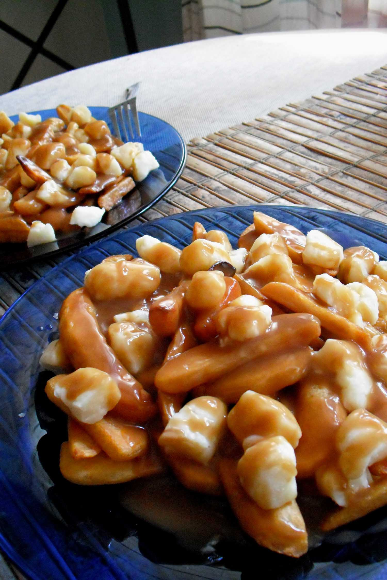 Typical Canadian food called poutine, gravy and cheese on fries on a blue plate