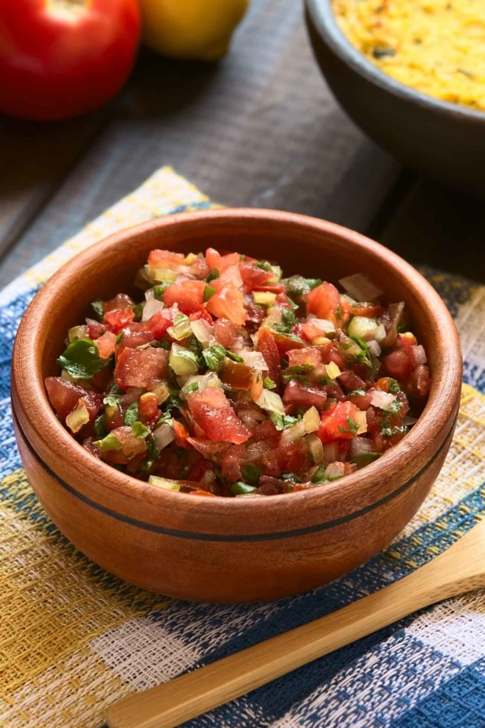 Traditional pico de gallo or Chilean Pebre sauce made of tomato onion aji verde (small green hot pepper) lemon juice and coriander leaves served for barbecue and traditional dishes photographed on wood with natural light (Selective Focus Focus in the middle of the pebre)
