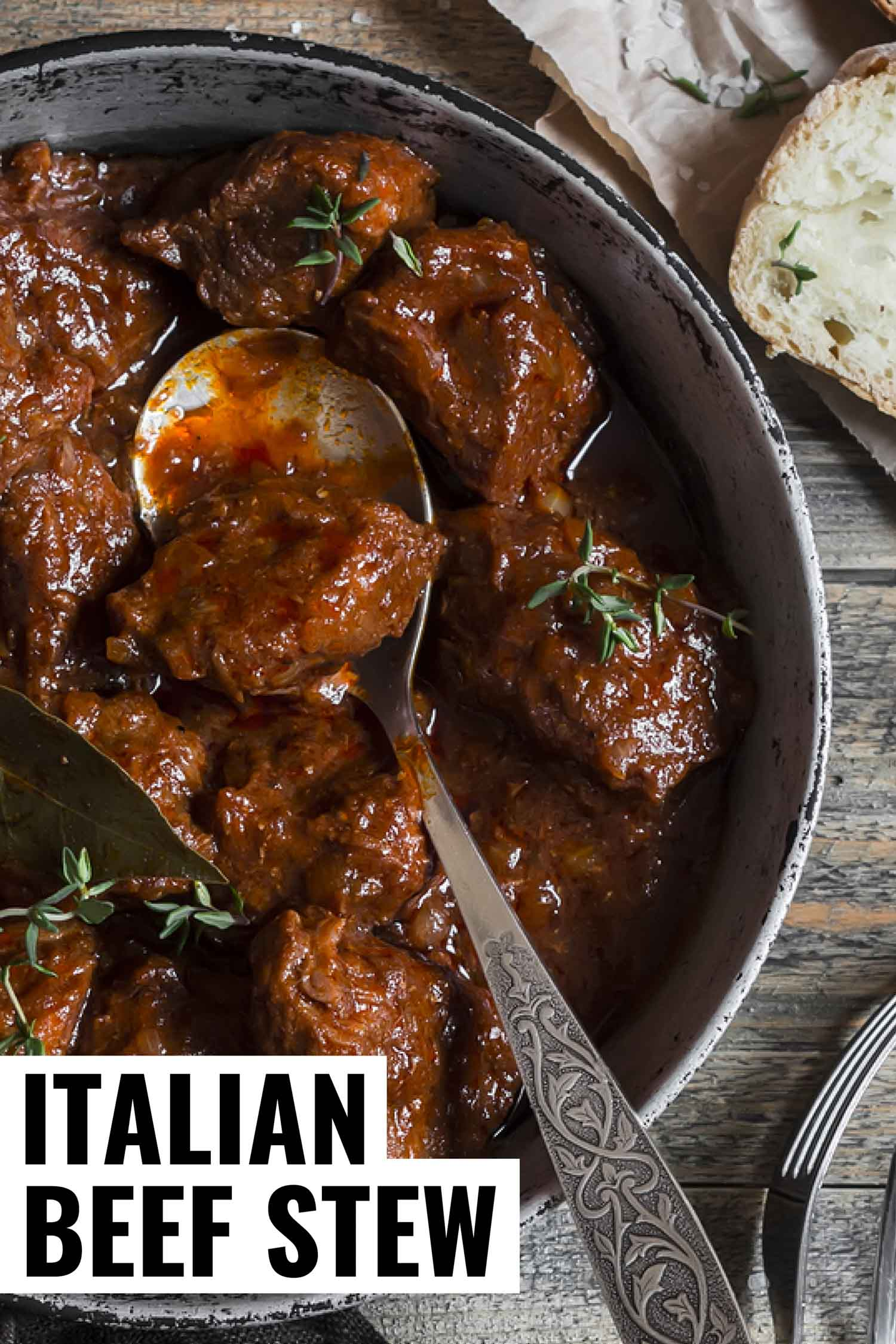 Italian beef stew braised in red wine in a grey pot on a grey rustic background