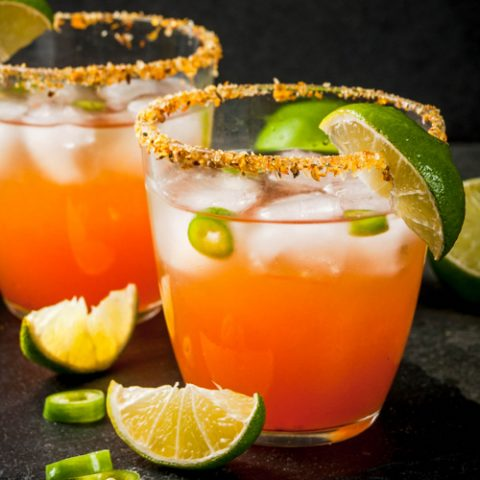 Mexican Micheladas, a beer cocktail garnished with lime on a black background.