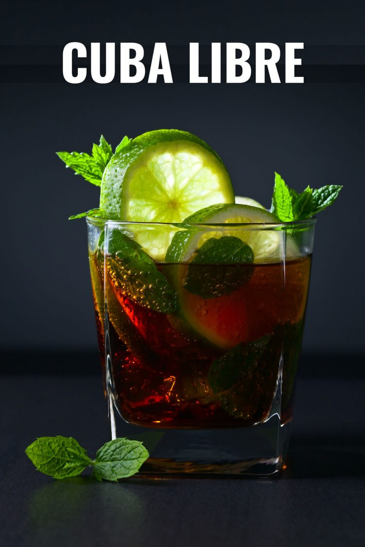 Cuba libre cocktail in a glass garnished with lime on a black background.