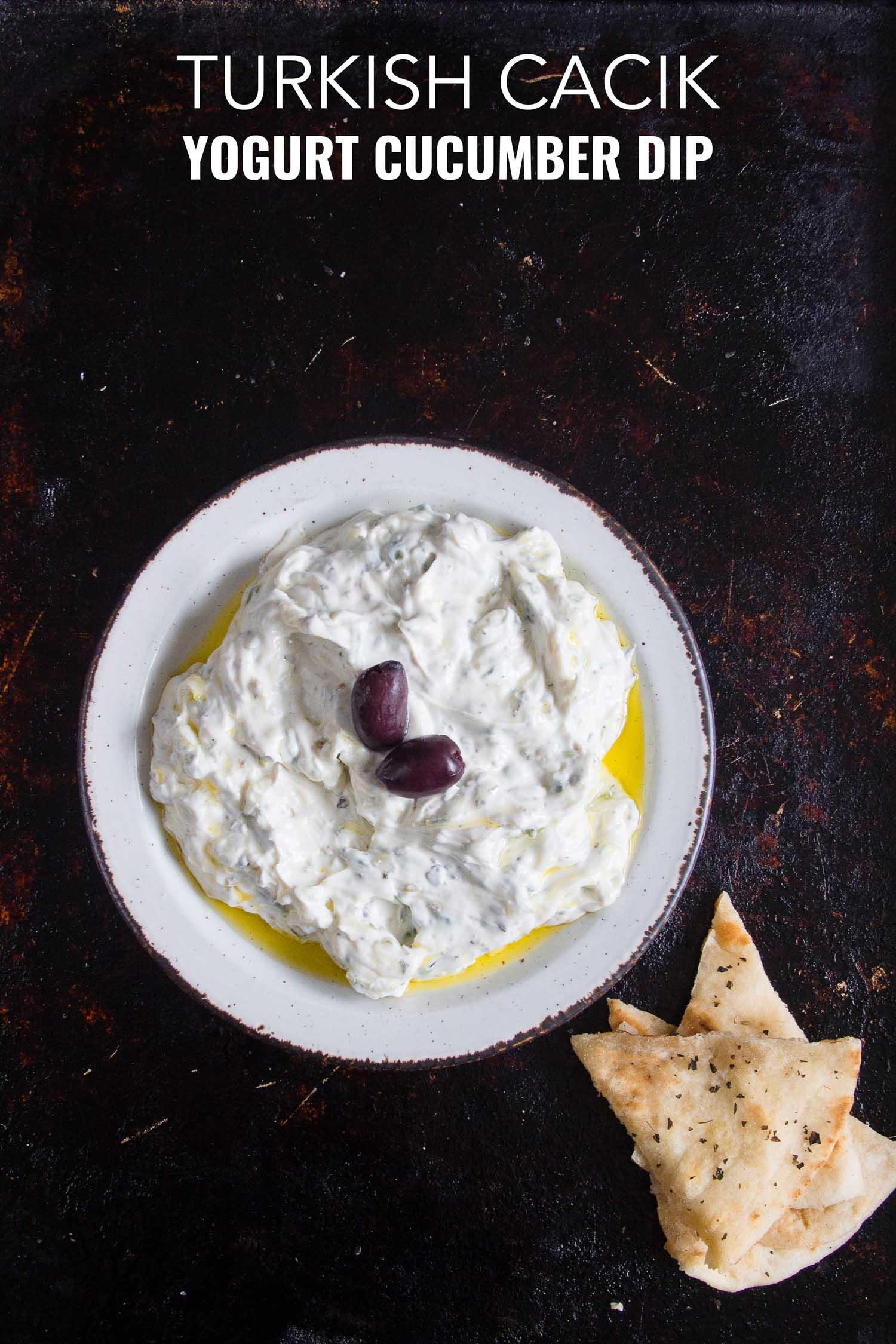 Turkish cucumber yogurt dip on a white plate and black background