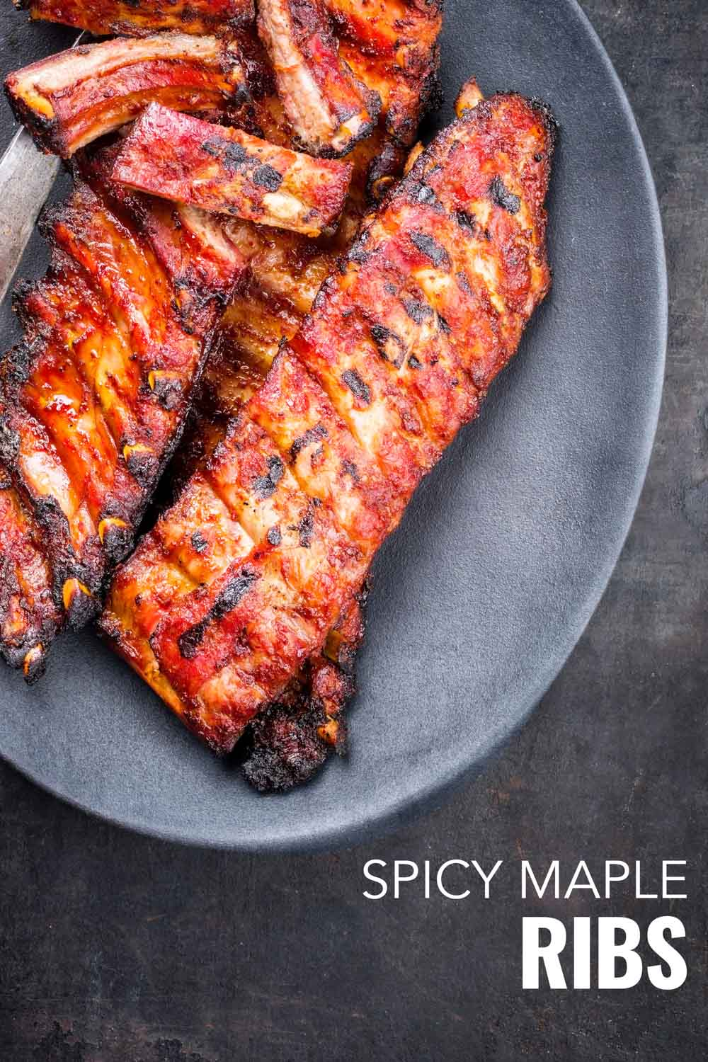 Spicy maple ribs uncut on a grey plate on a grey background.