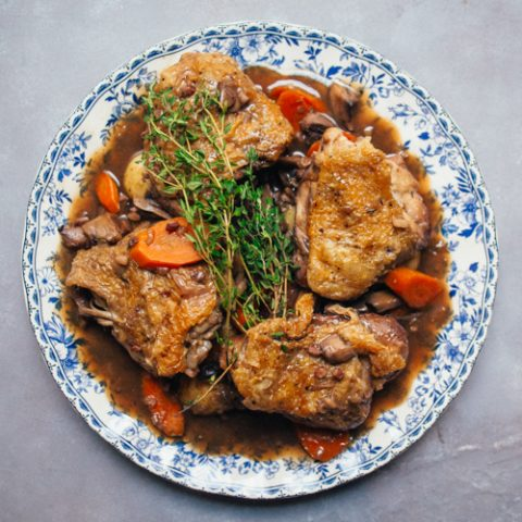Coq au Vin on a plate on a grey background