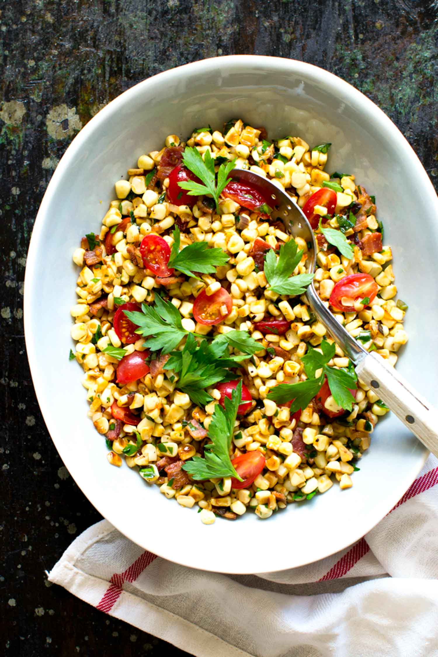 Warm corn salad with ramps in white bowl on black background.