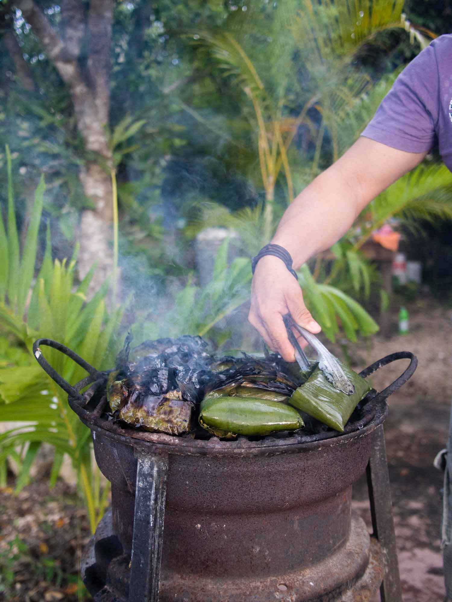 Grilling tamales in banana leaves.