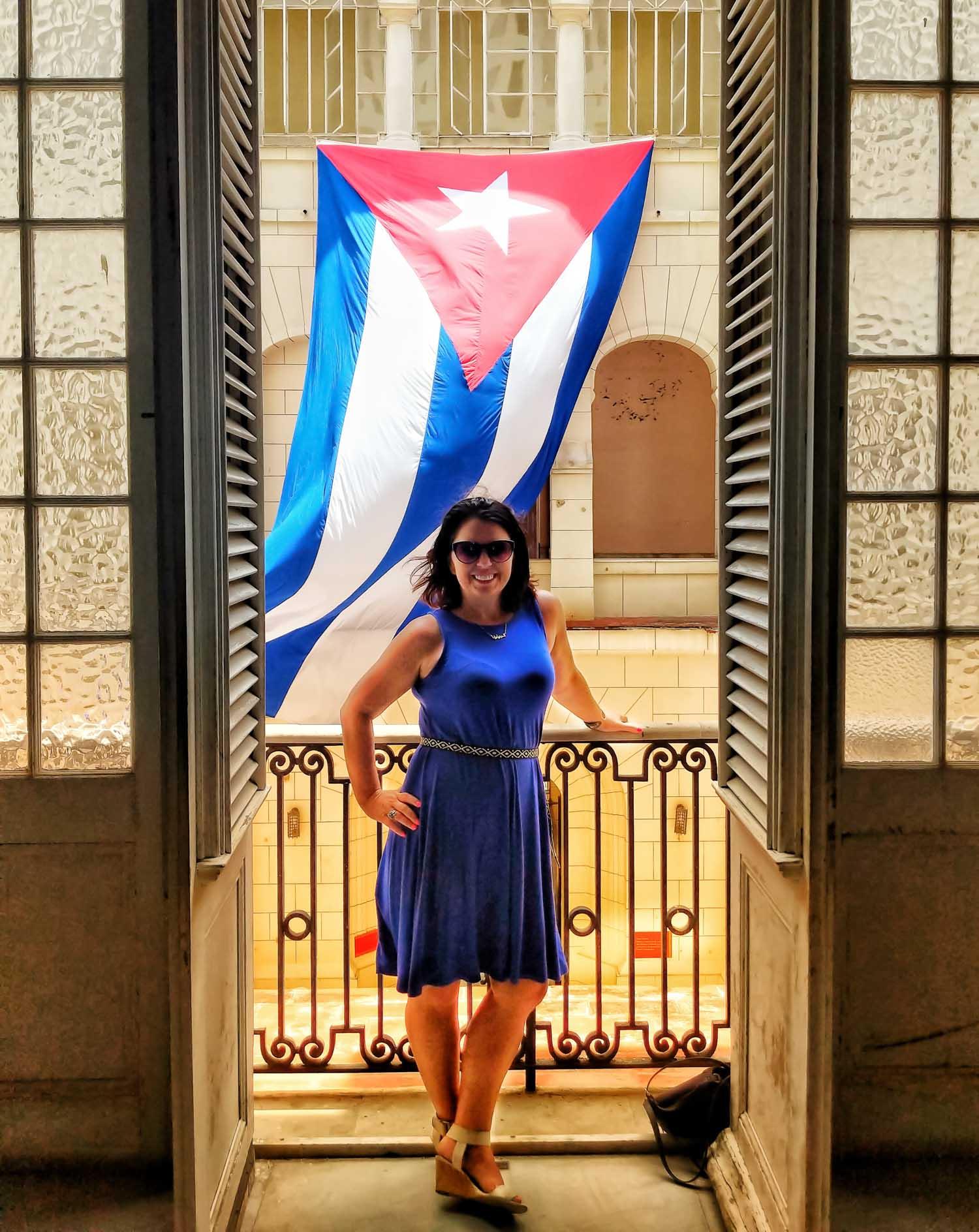 Ayngelina Brogan standing in front of Cuban flag at the museum of revolution in Havana Cuba