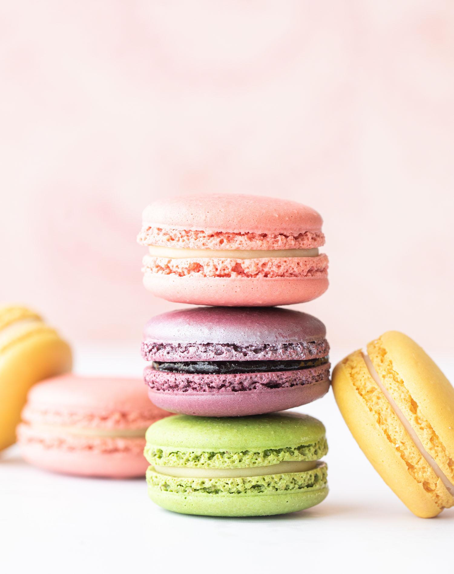 stack of French macarons on pink background