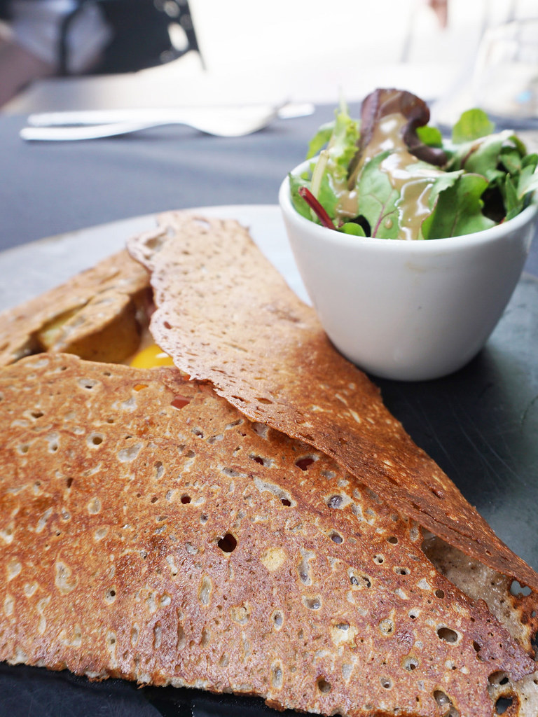 Traditional French galette with bowl of salad on the side.