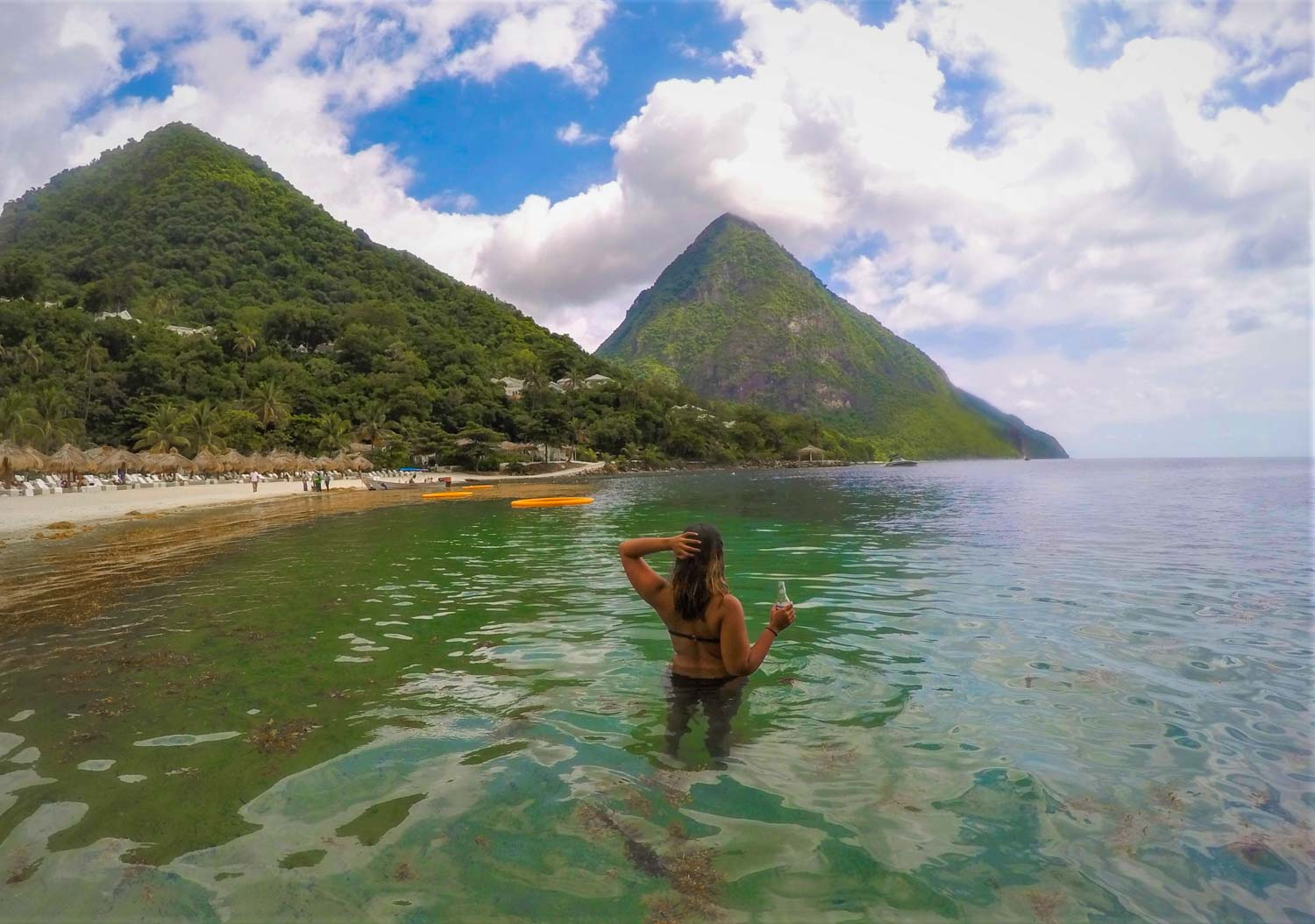 Woman in water at Jalousie beach in St.Lucia with mountains in background.