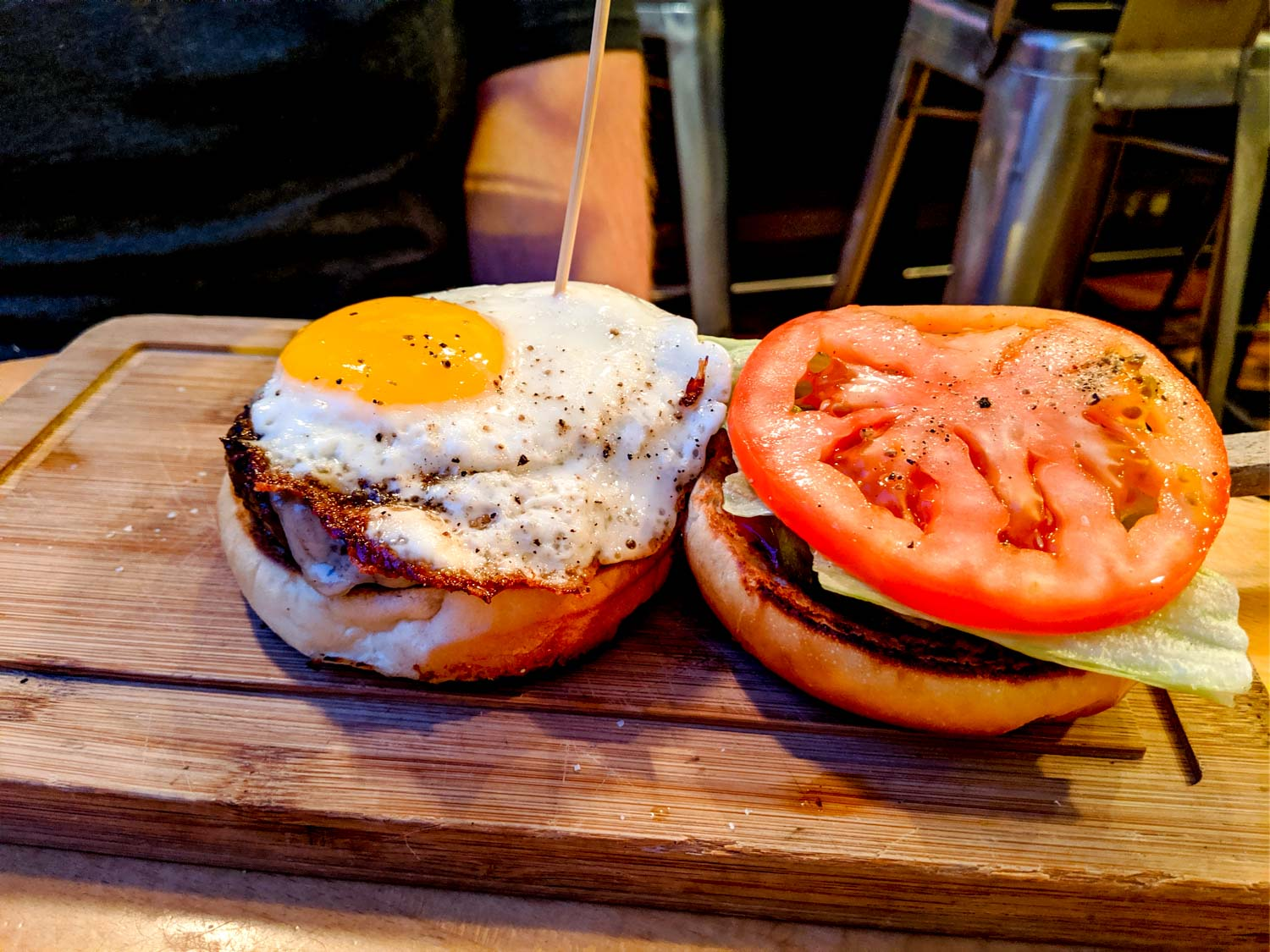 The butcher and burger with an egg, lettuce, tomato on a beef patty.