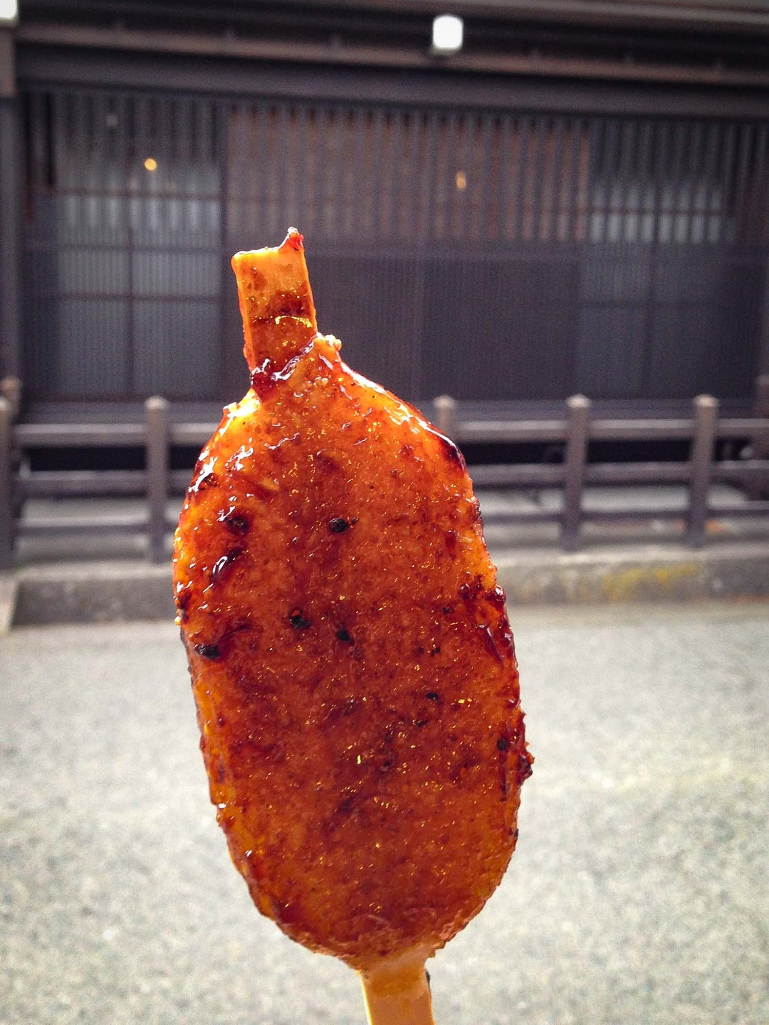 Goheimochi sticky rice on a stick with soy or mirin sauce