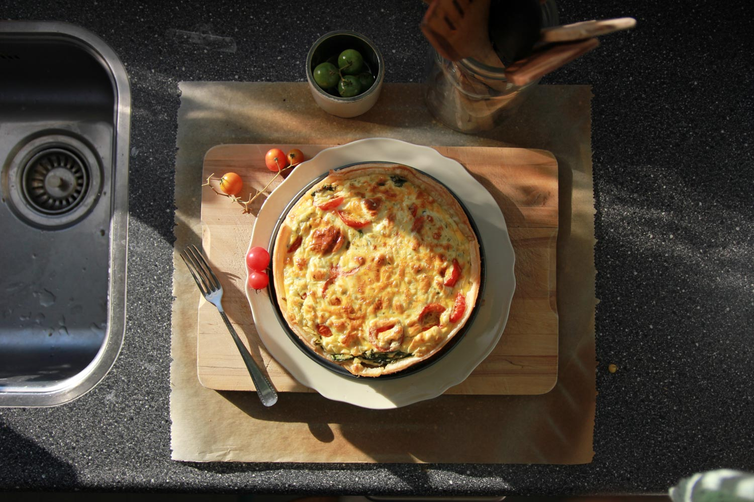 Traditional French cuisine, Quiche Lorraine on a cutting board in the sunshine.