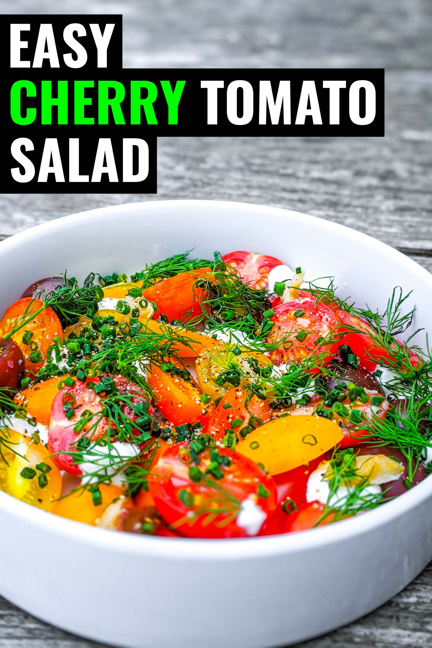 Fresh cherry tomato salad with herbs and creme fraiche in white bowl on grey wood background