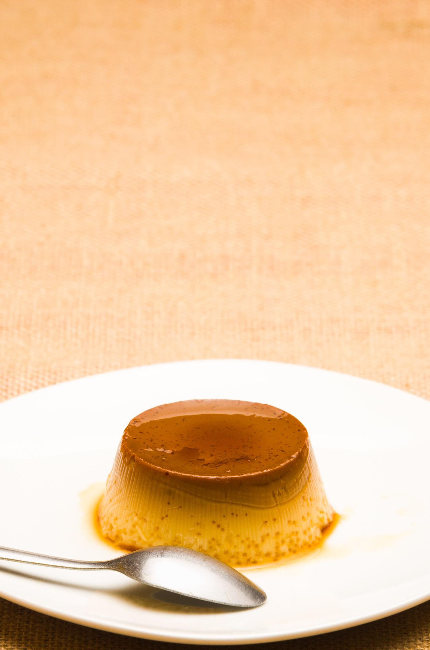 Caramel flan on a white plate.