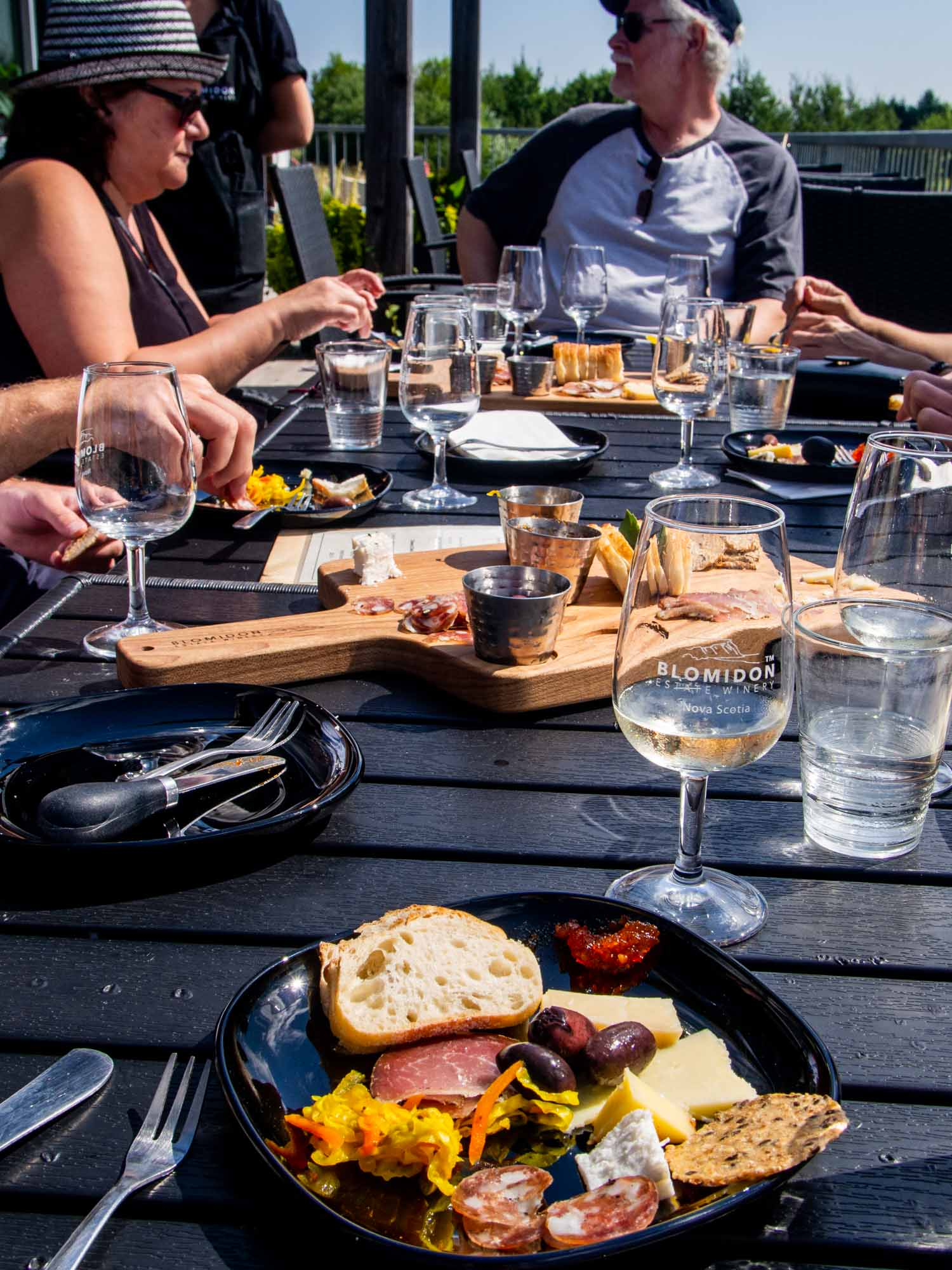 Blomidon Estate Winery in Canning Nova Scotia, people at table drinking Nova Scotia wine and eating charcuterie.