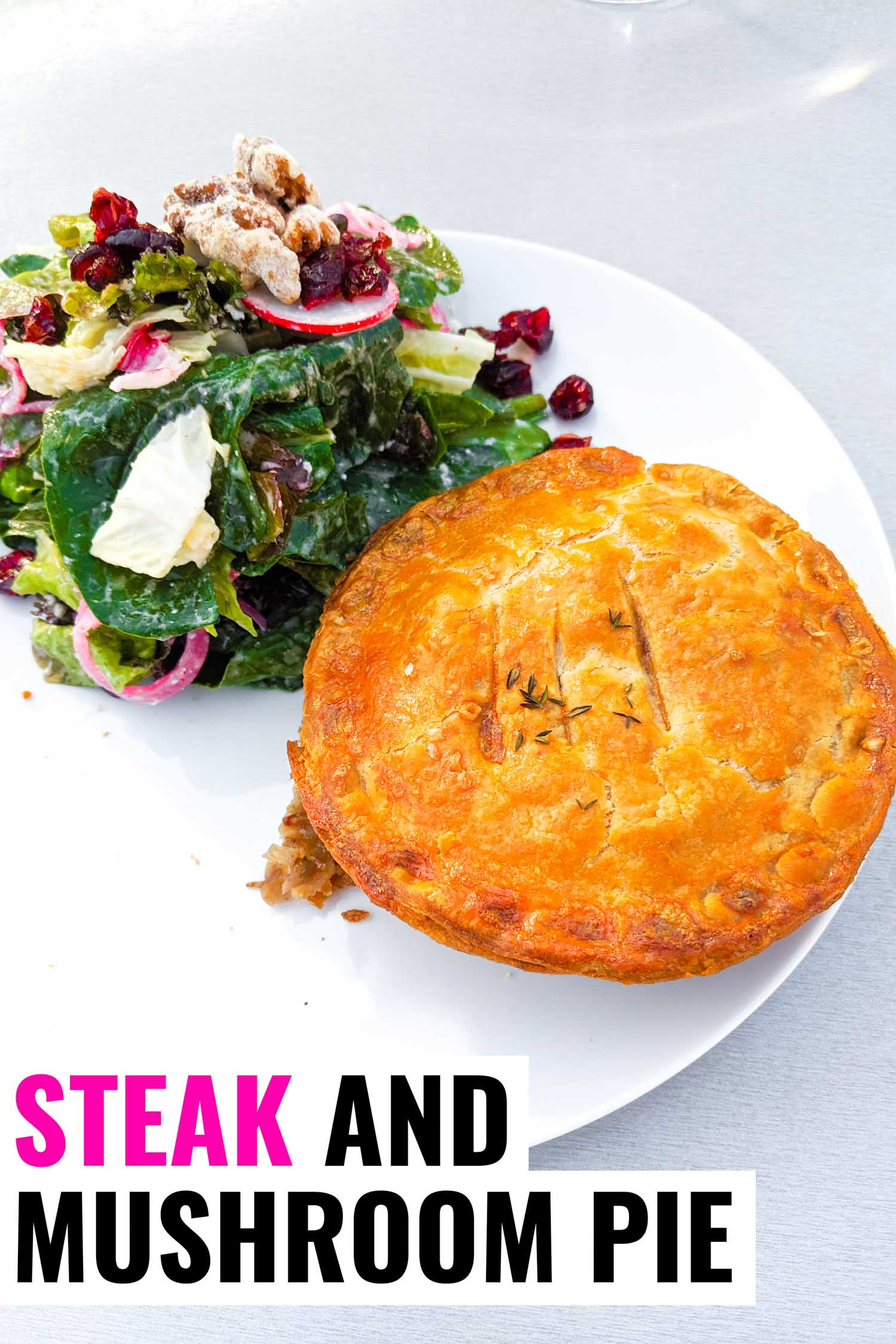Steak and mushroom pie recipe on a plate with a green salad.