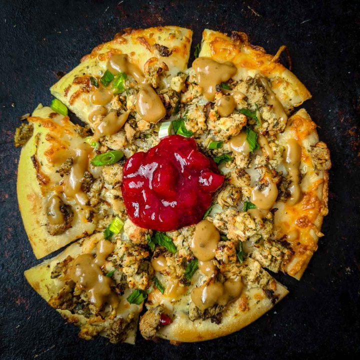 Christmas pizza or thanksgiving pizza using turkey dinner leftovers on black.