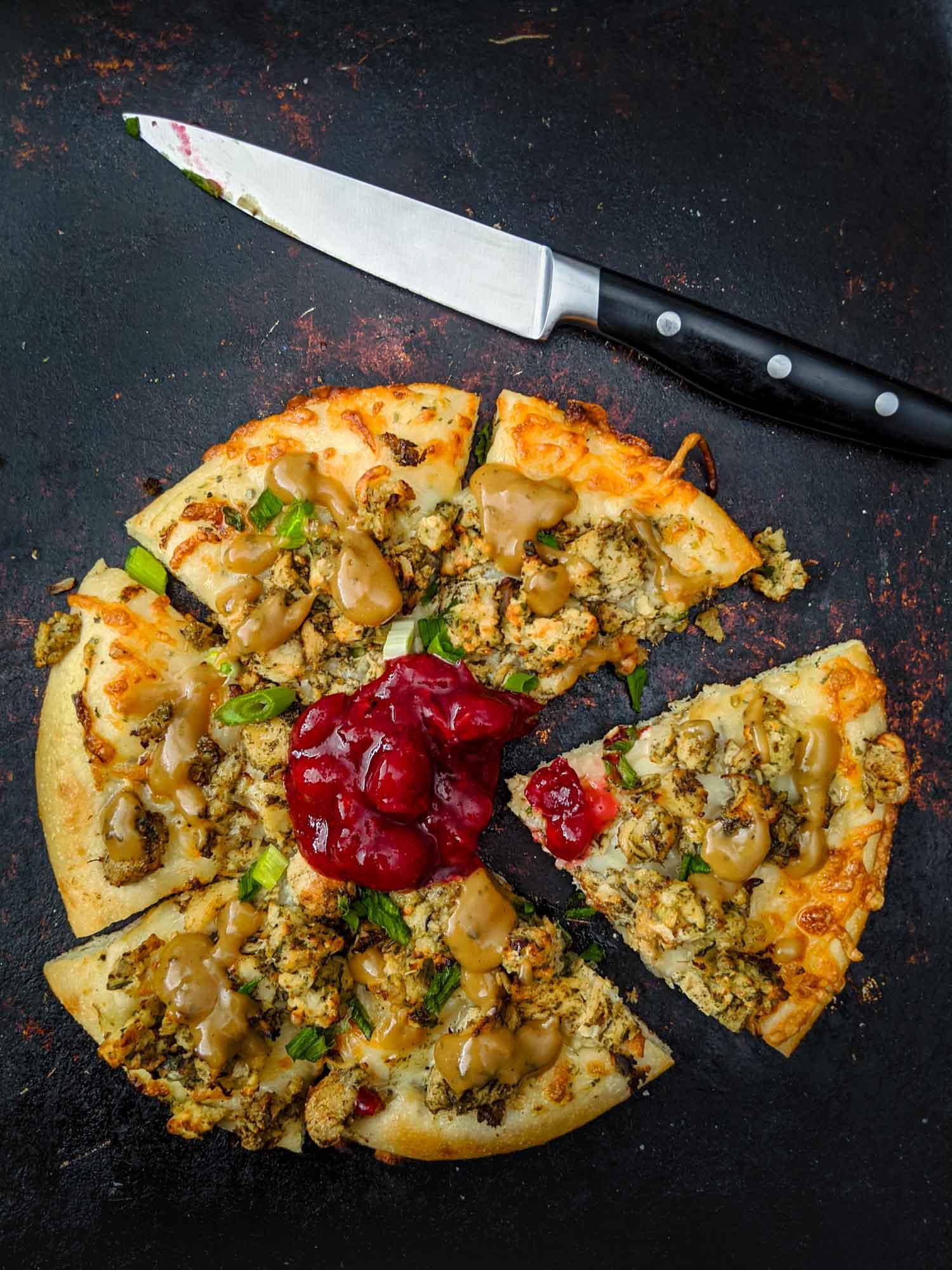Thanksgiving pizza using turkey dinner leftovers on black.