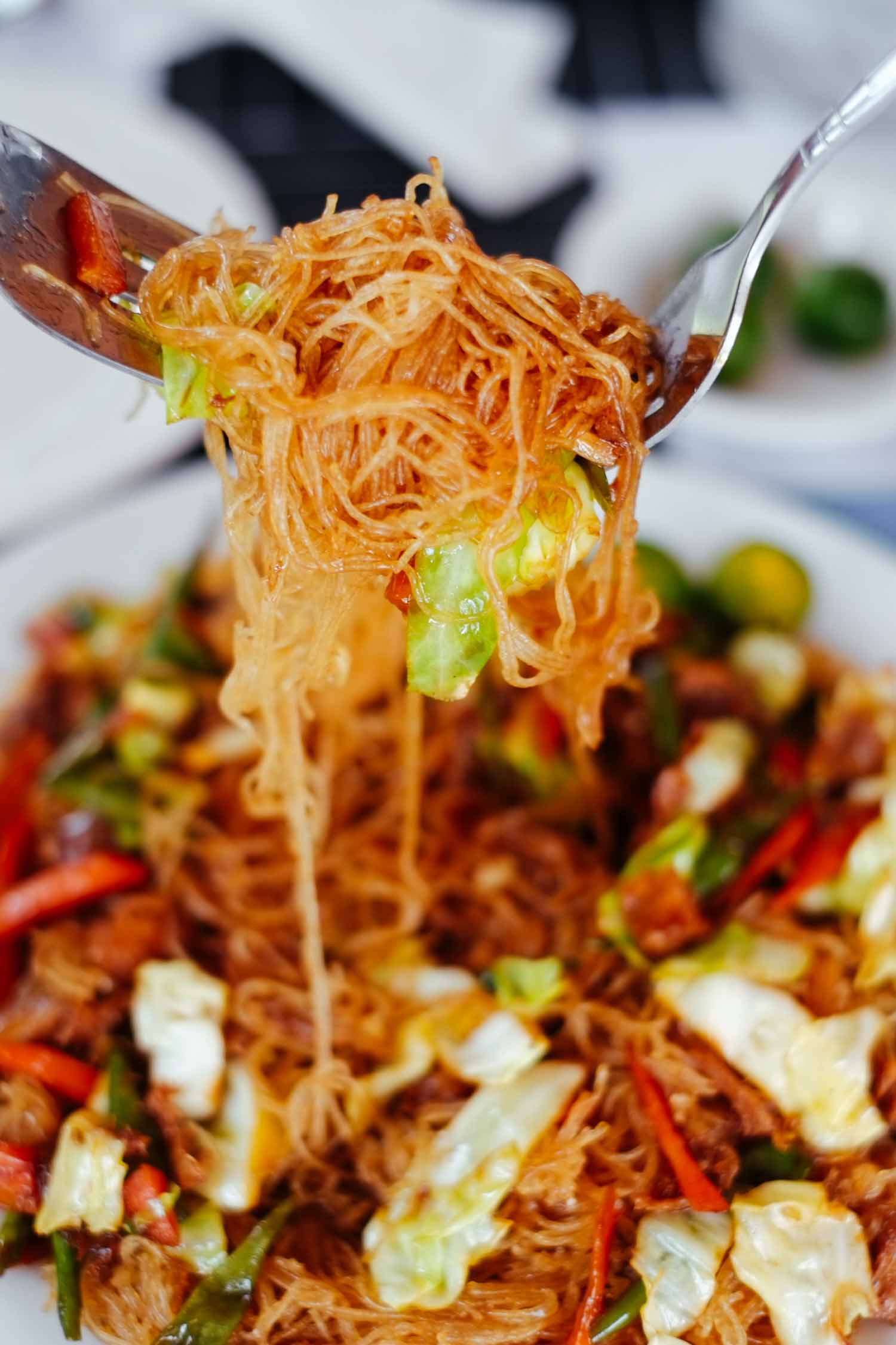 Pancit noodles held on a fork above a Filipino food dish