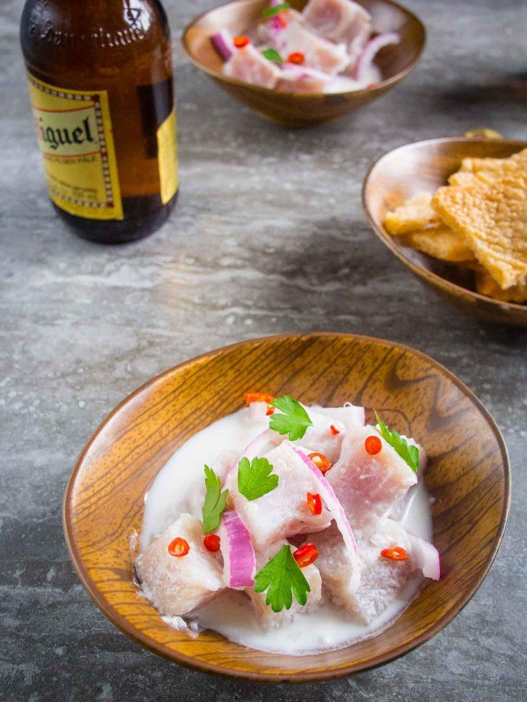 Kinilaw is a common Filipino food similar to ceviche. It is in a pork on a table with beer and chicharron served next to it.