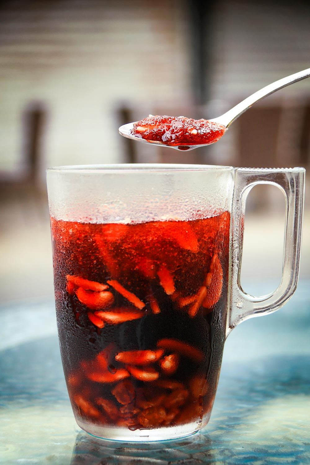 A spoon above a jallab tall glass. Jallab is a refreshing summer drink, popular during Ramadan. It's made of grape, carob molasses, dates, and rose water. It is diluted in water with crushed ice, nuts, and raisins.