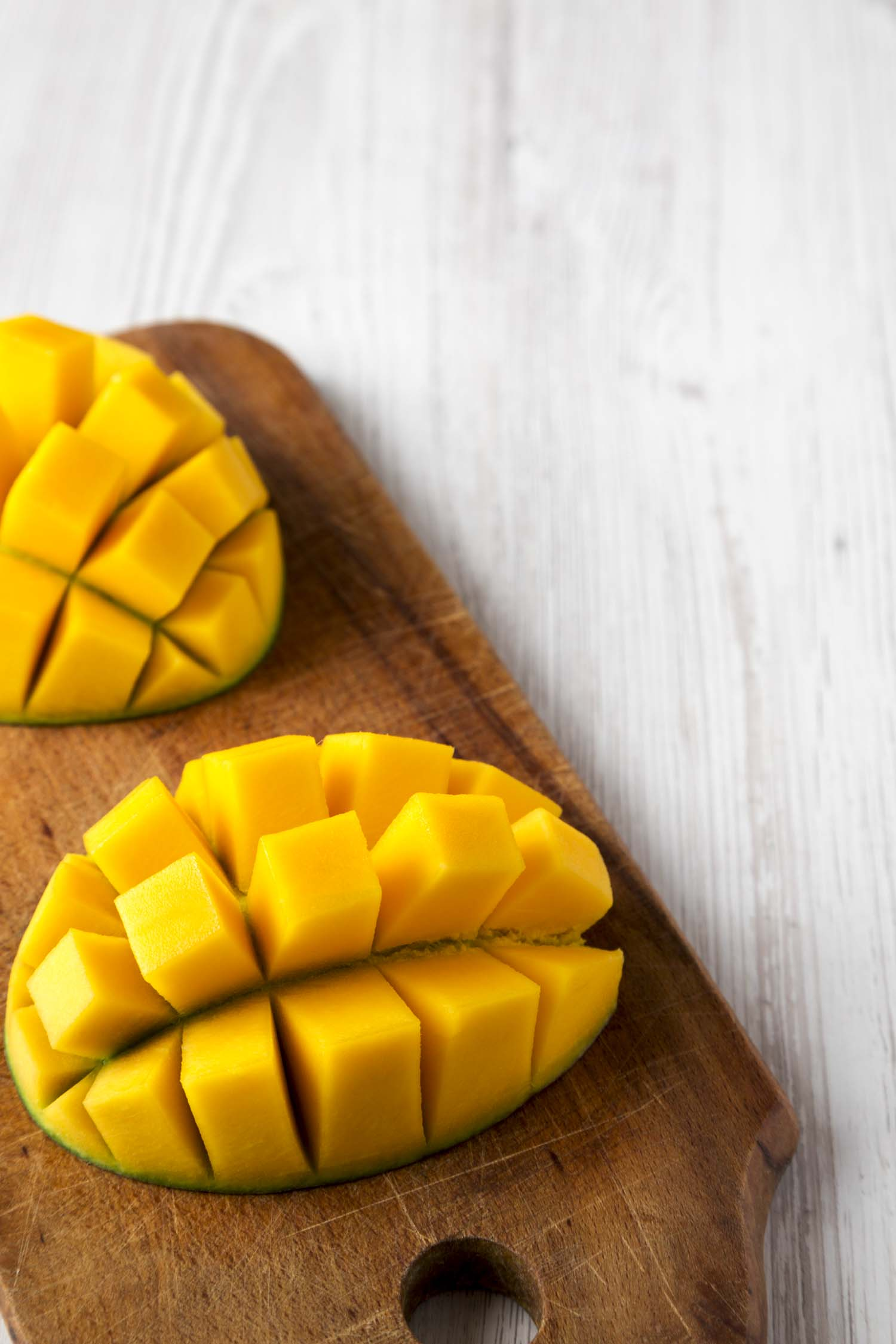 Sweet mango on rustic wooden board on a white wooden table, low angle view. Close-up. Copy space.