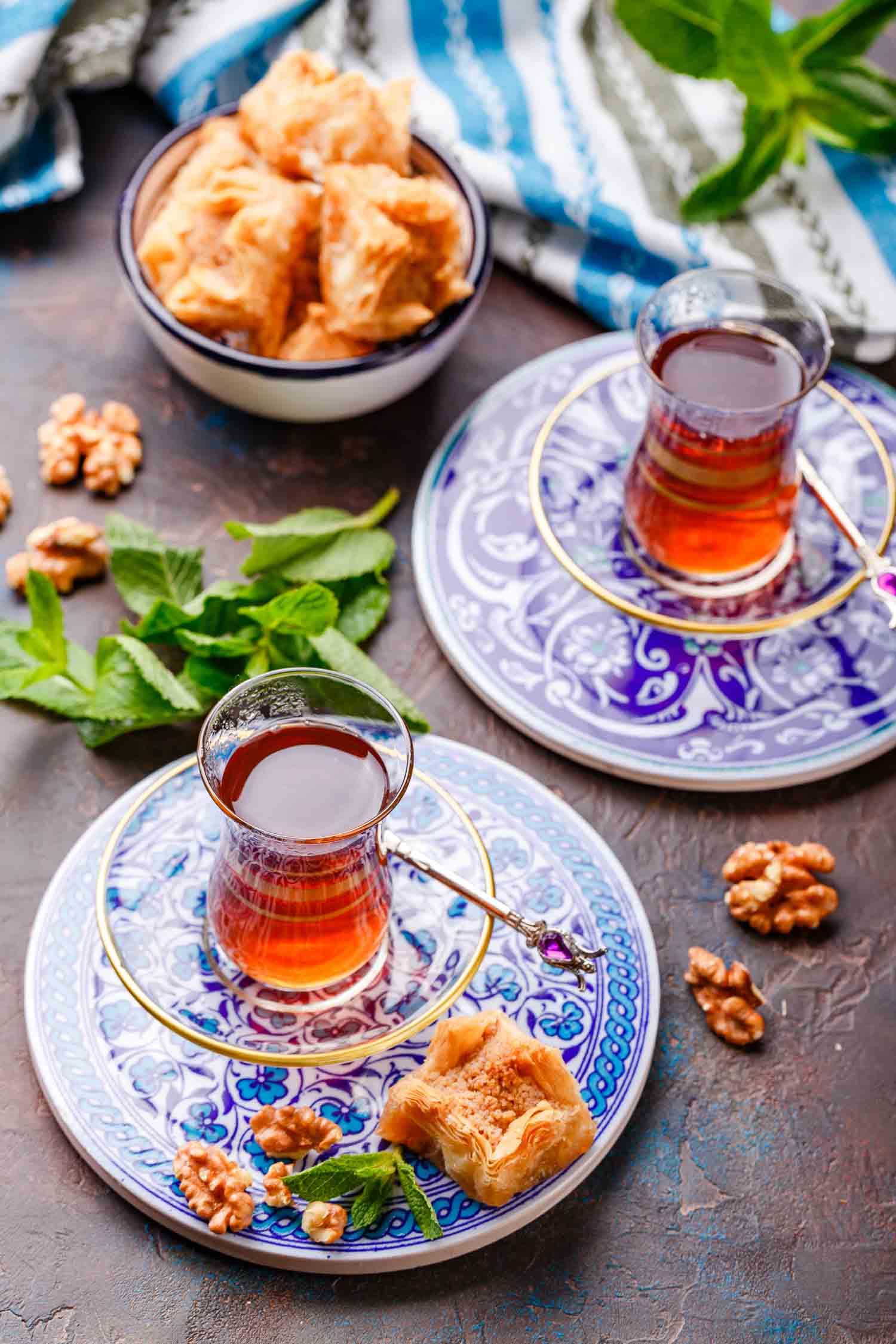Middle Eastern or Arabic tea with mint in a traditional glass cup and Turkish sweetness Baklava. Ramadan kareem. Eid mubarak. Islamic holidays decoration.