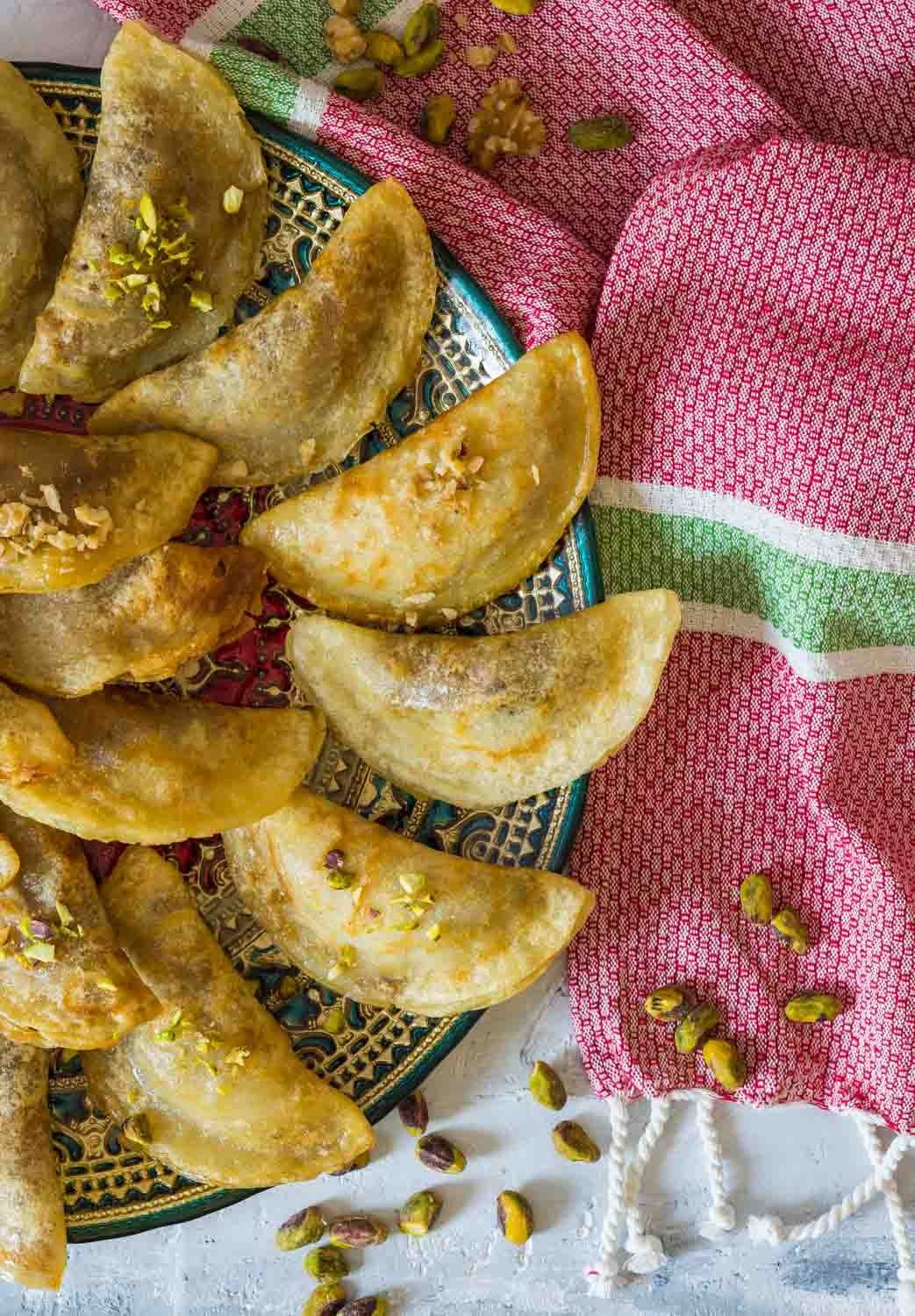 Arabic Traditional dessert Qatayef or Atayef served with sugar and rose syrup and roasted nuts.