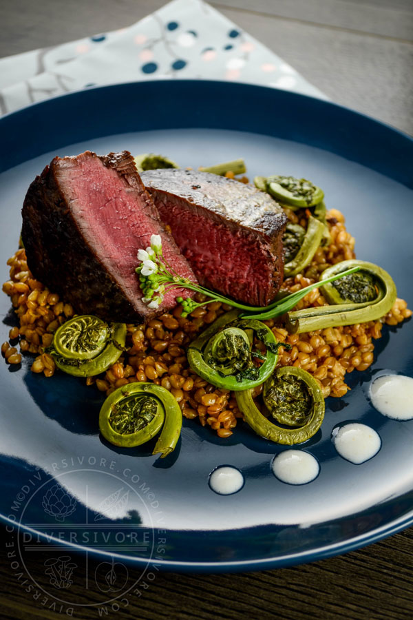 Beef tenderloin with fiddleheads on a blue plate