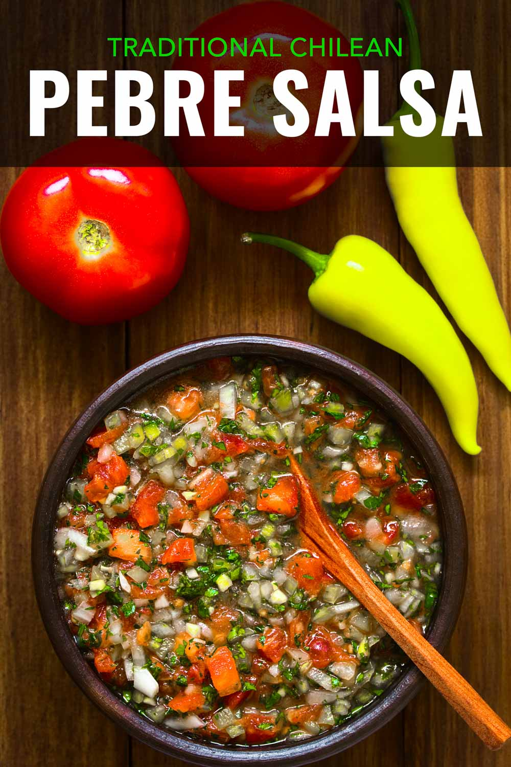 Bowl of cilantro salsa on a table with tomatoes and aji peppers