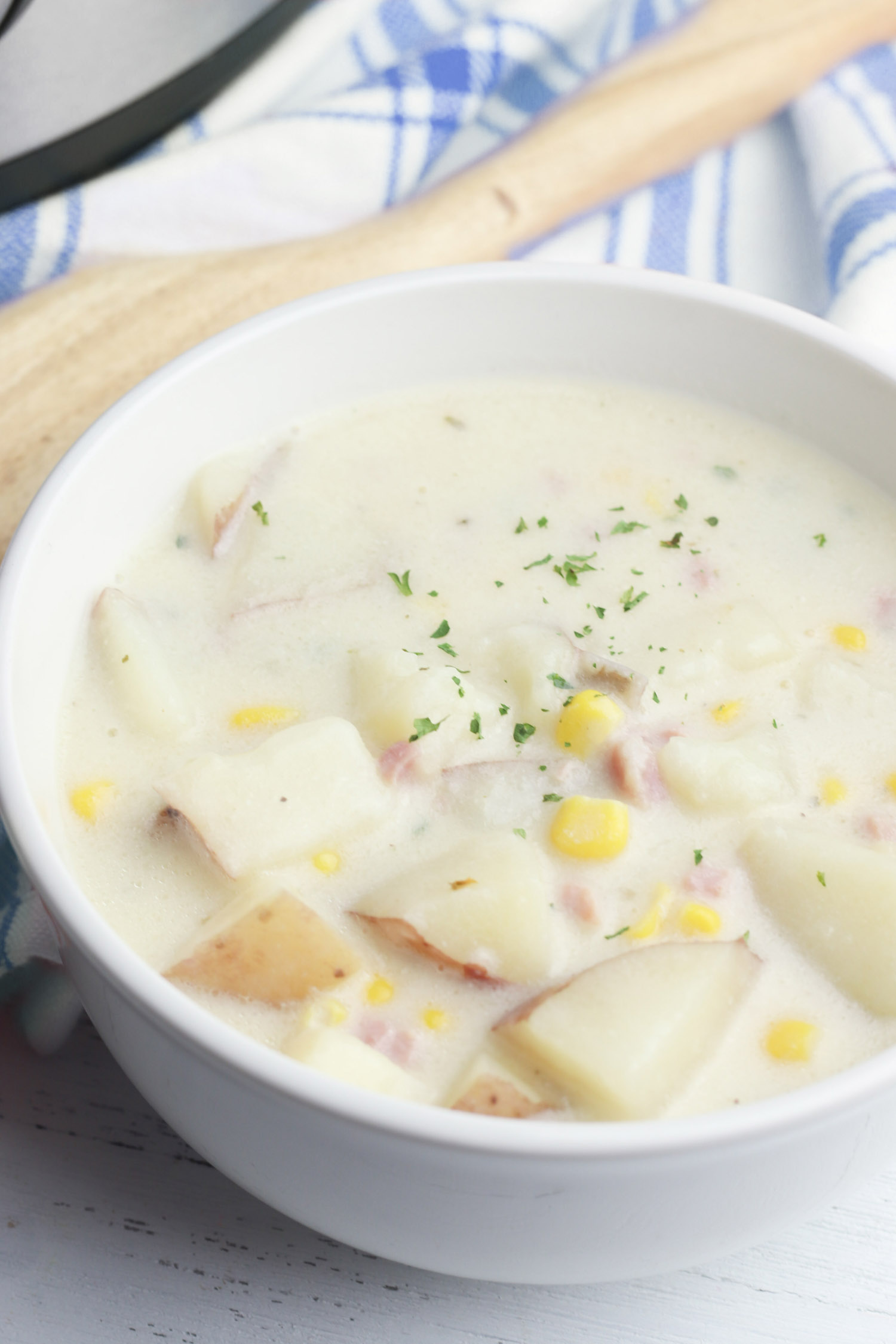 Creamy corn soup in a white bowl in a kitchen.