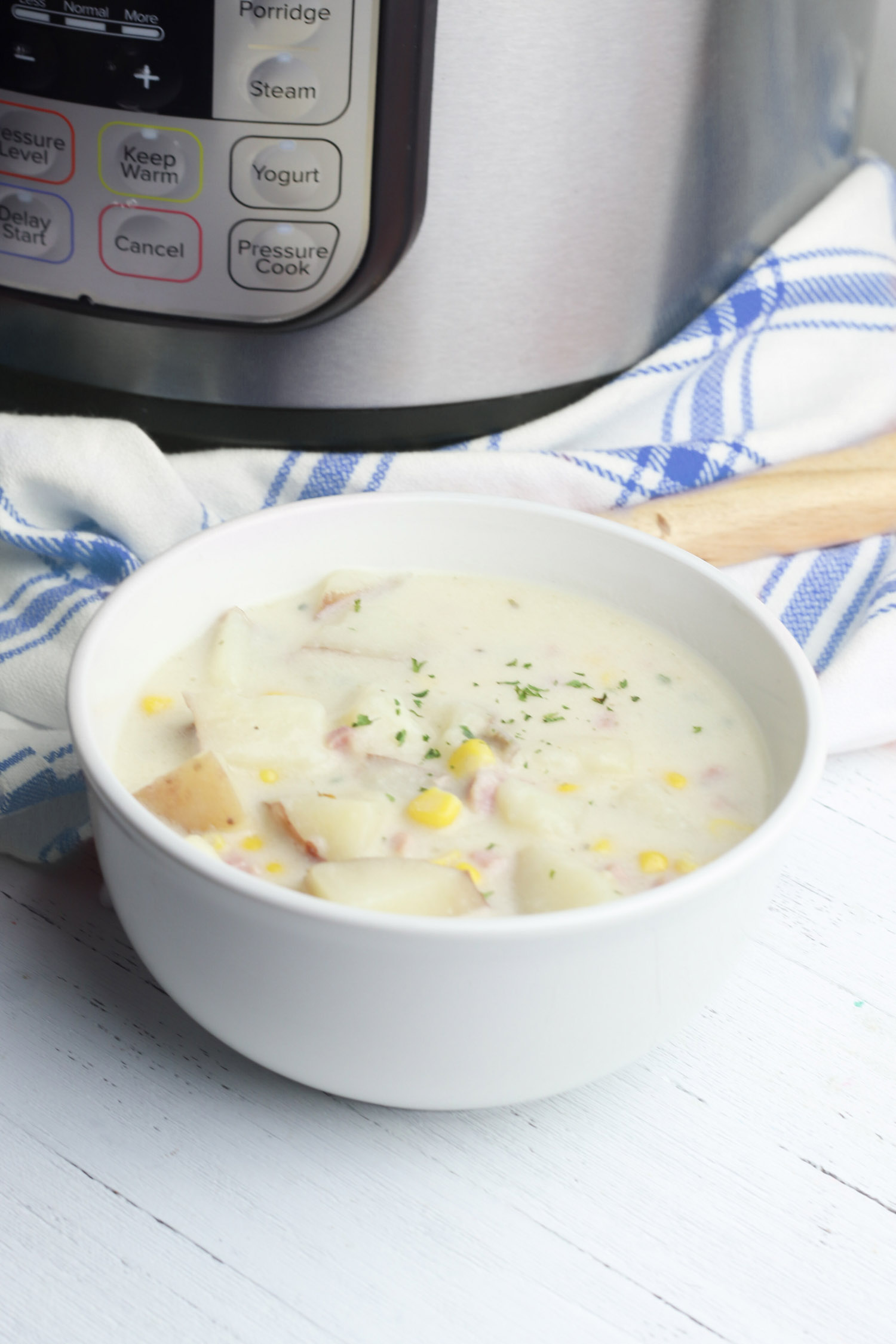 bowl of corn chowder next to an instant pot