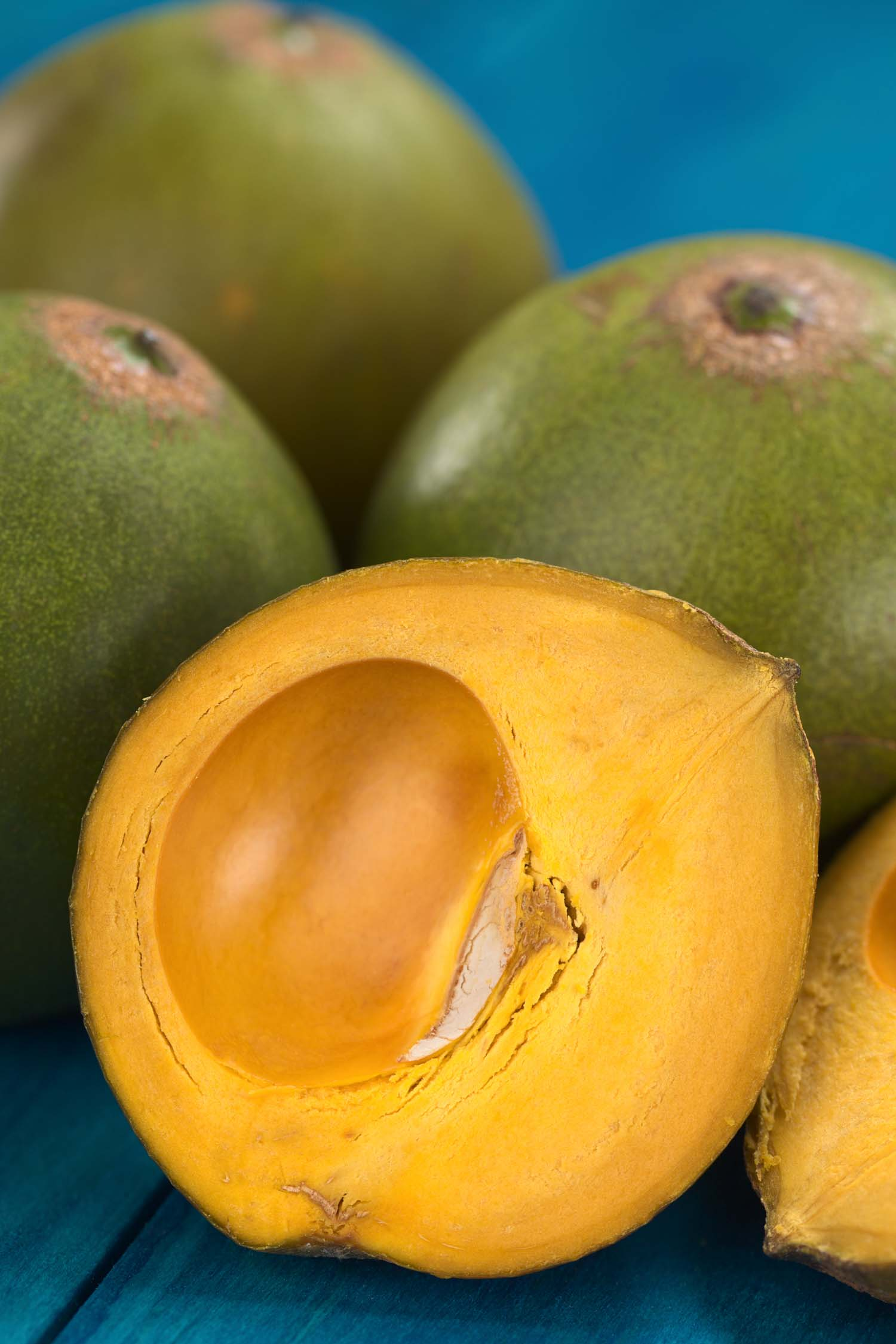 Peru fruit called Lucuma (lat. Pouteria lucuma) which has a dry sweet flesh and is mostly used to prepare juices milkshakes yogurts ice cream and other desserts (Selective Focus Focus on the front of the standing lucuma half)