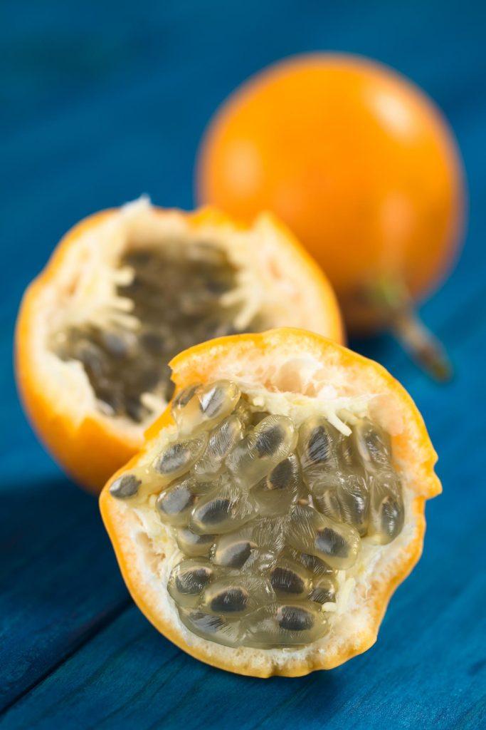 Peru fruit sweet granadilla or grenadia (lat. Passiflora ligularis) fruit cut in half of which the seeds and the surrounding juicy pulp is eaten or is used to prepare juice