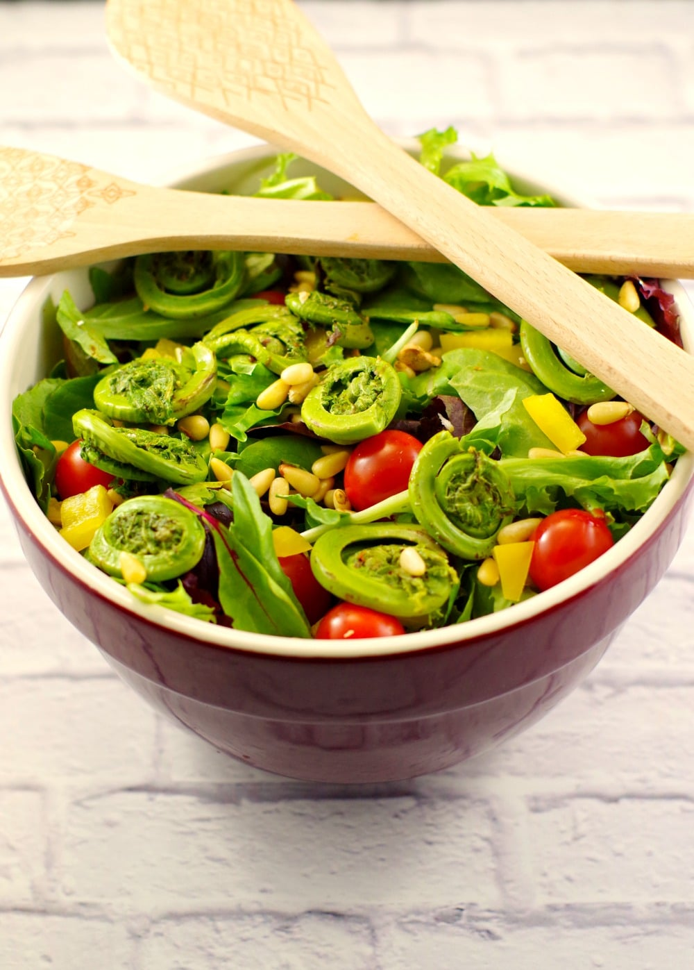Salad with fiddleheads and blackberry vinaigrette in a large bowl with tongs