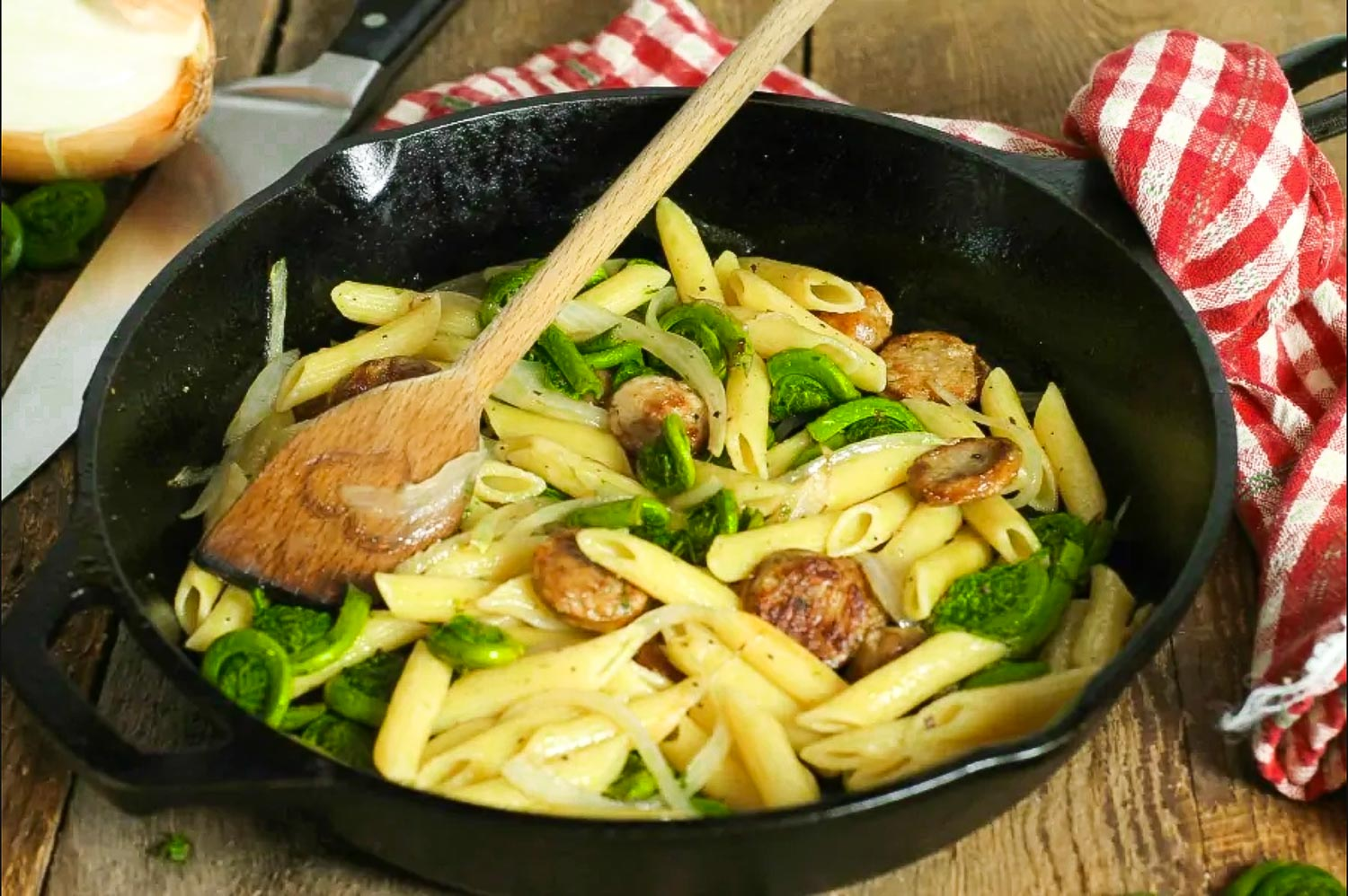 Fiddleheads penne pasta in a cast iron frying pan with a wooden fork