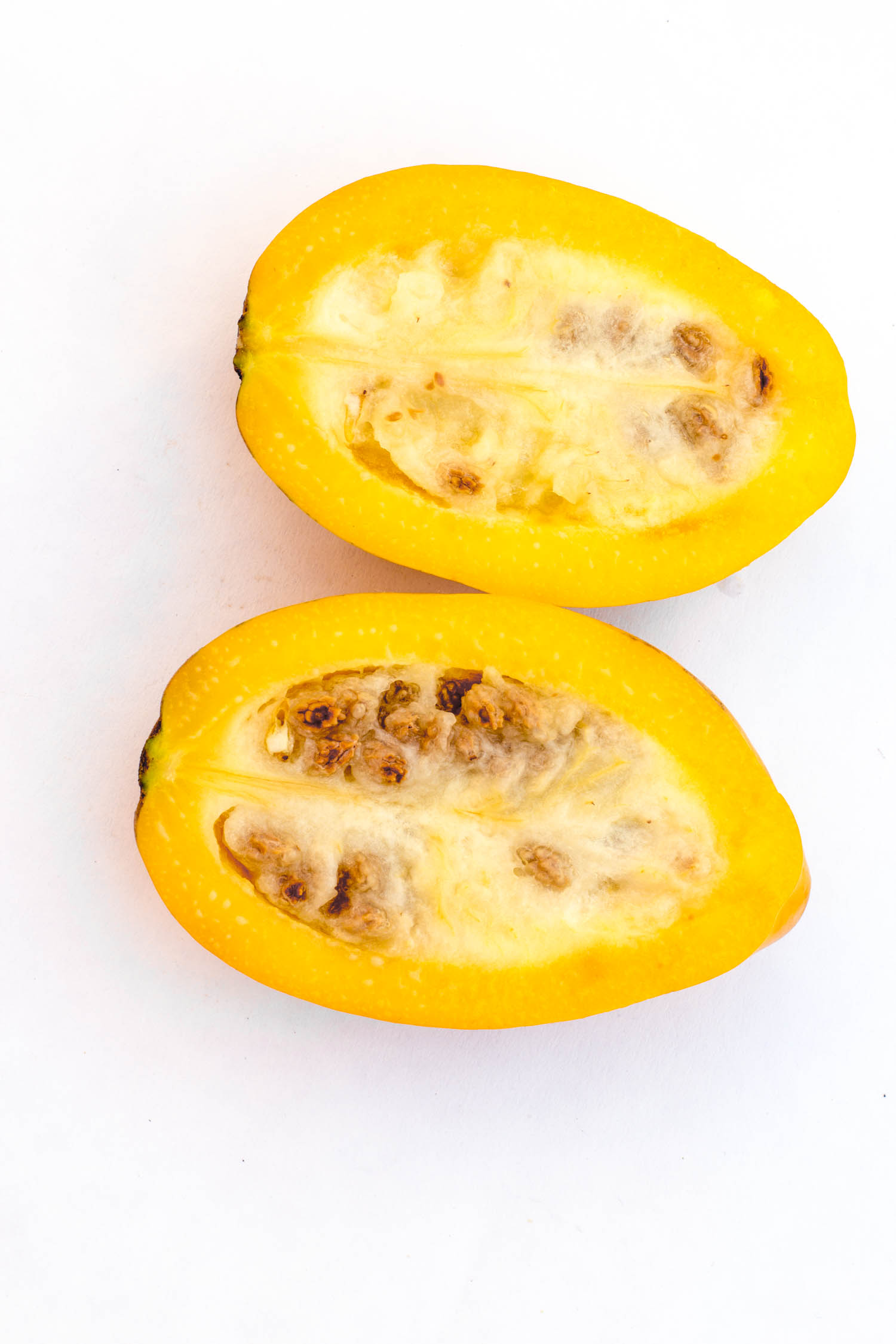 """Fresh and tasty Arequipena papaya with seeds isolated on white, in Arequipa, Peru. Smaller than usual this papaya is called """"Papaya Arequipea""""."""