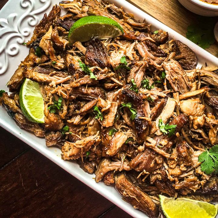 Mexican pork carnitas on a white tray with lime and cilantro