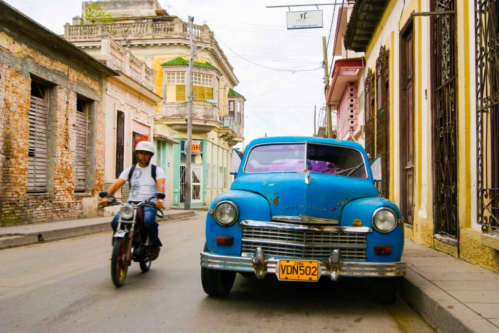 Santa Clara Cuba street with vintage car and motorcycle