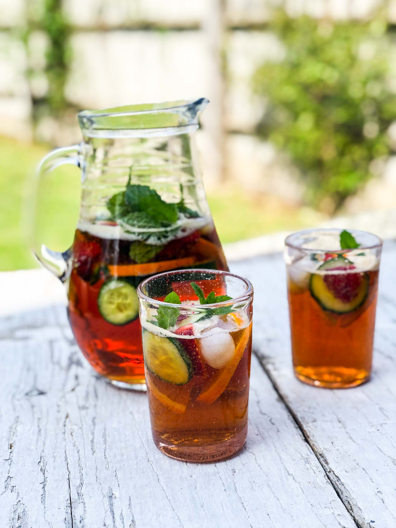 A pitcher of Pimm's with two glasses on a table.