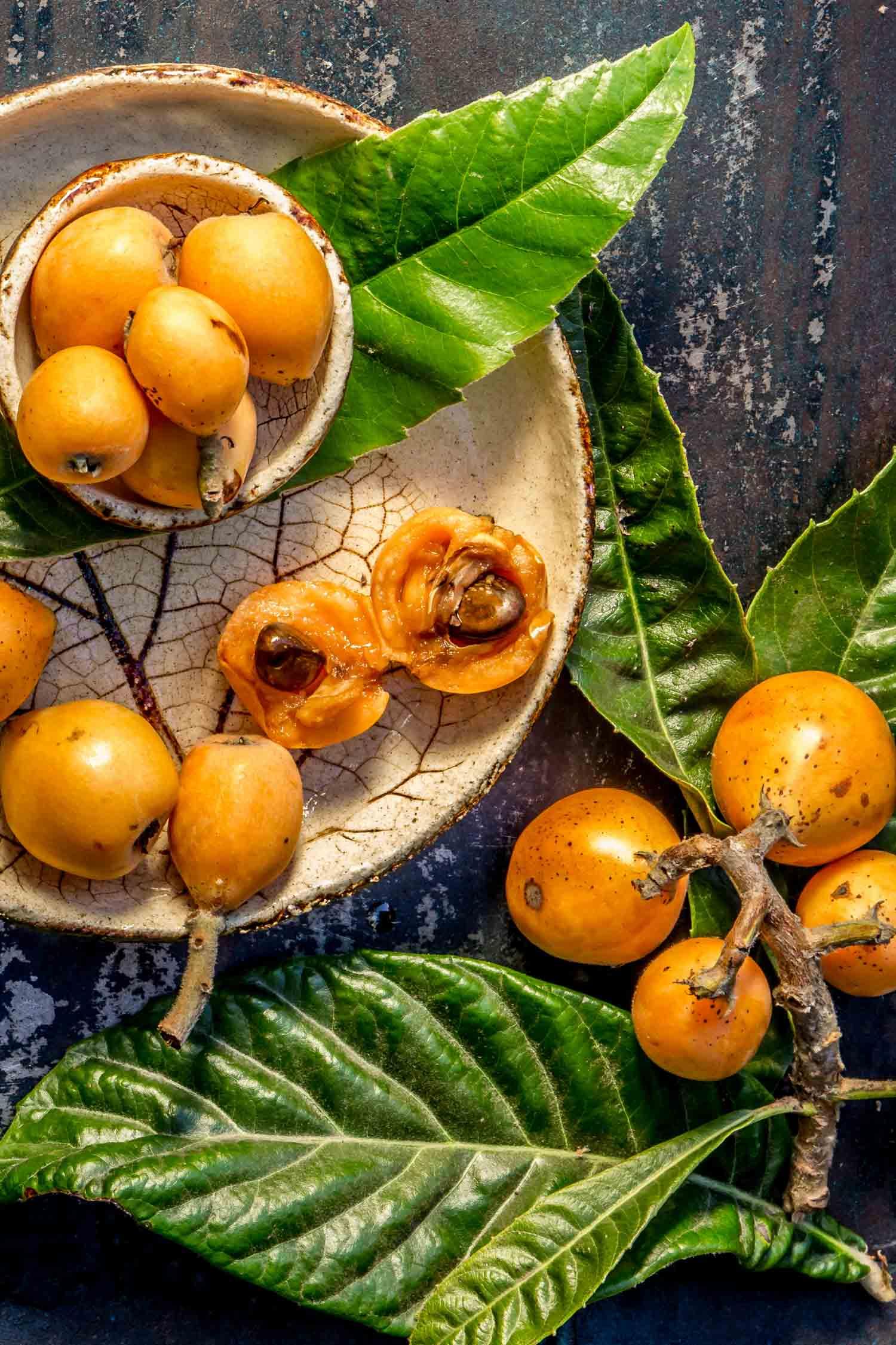 Hawaiian Loquat fruit. Nispero. Eriobotrya Japonica. Loquat with fresh leaves on metal background.