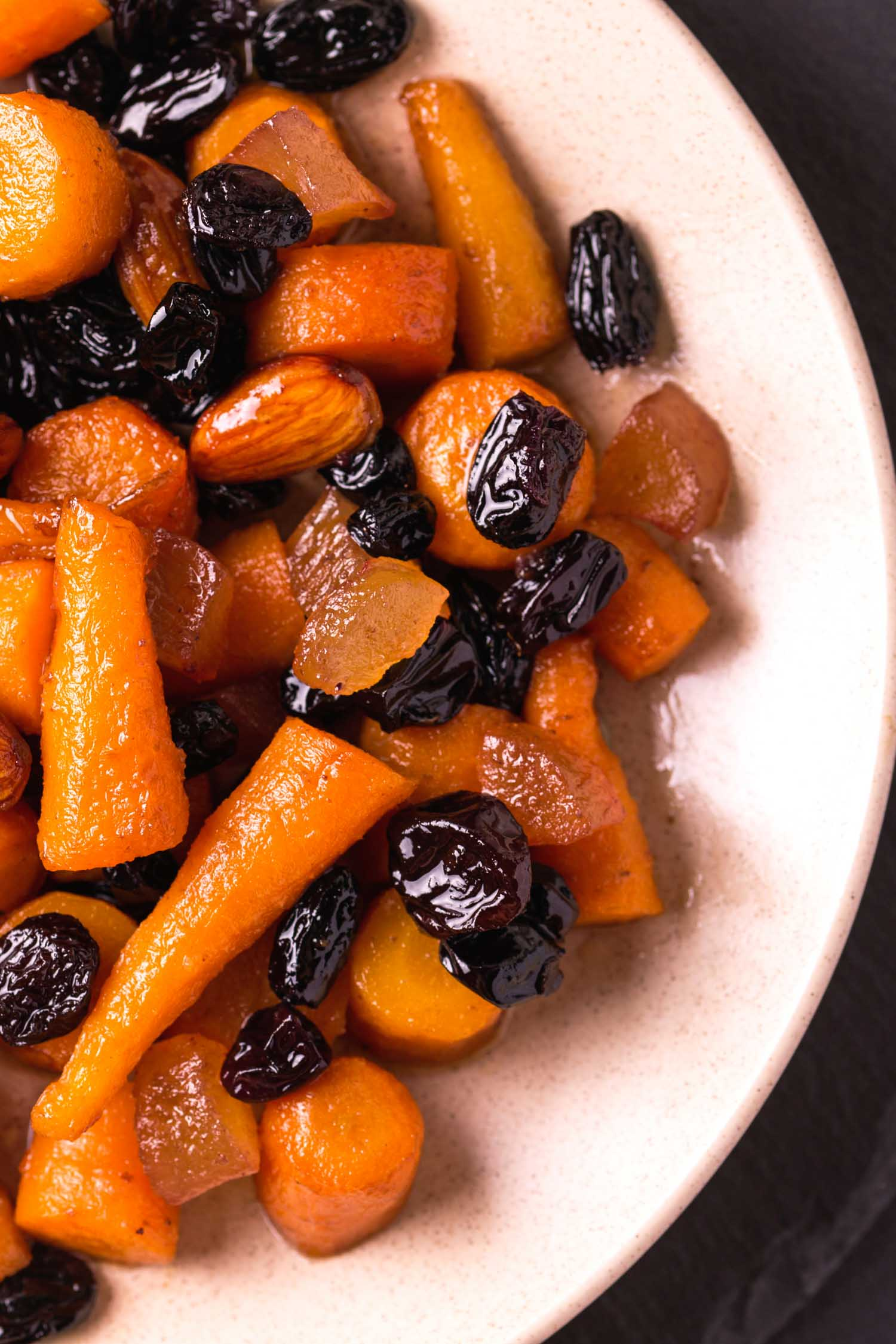 Tzimmes or carrots and dried fruits on a white plate