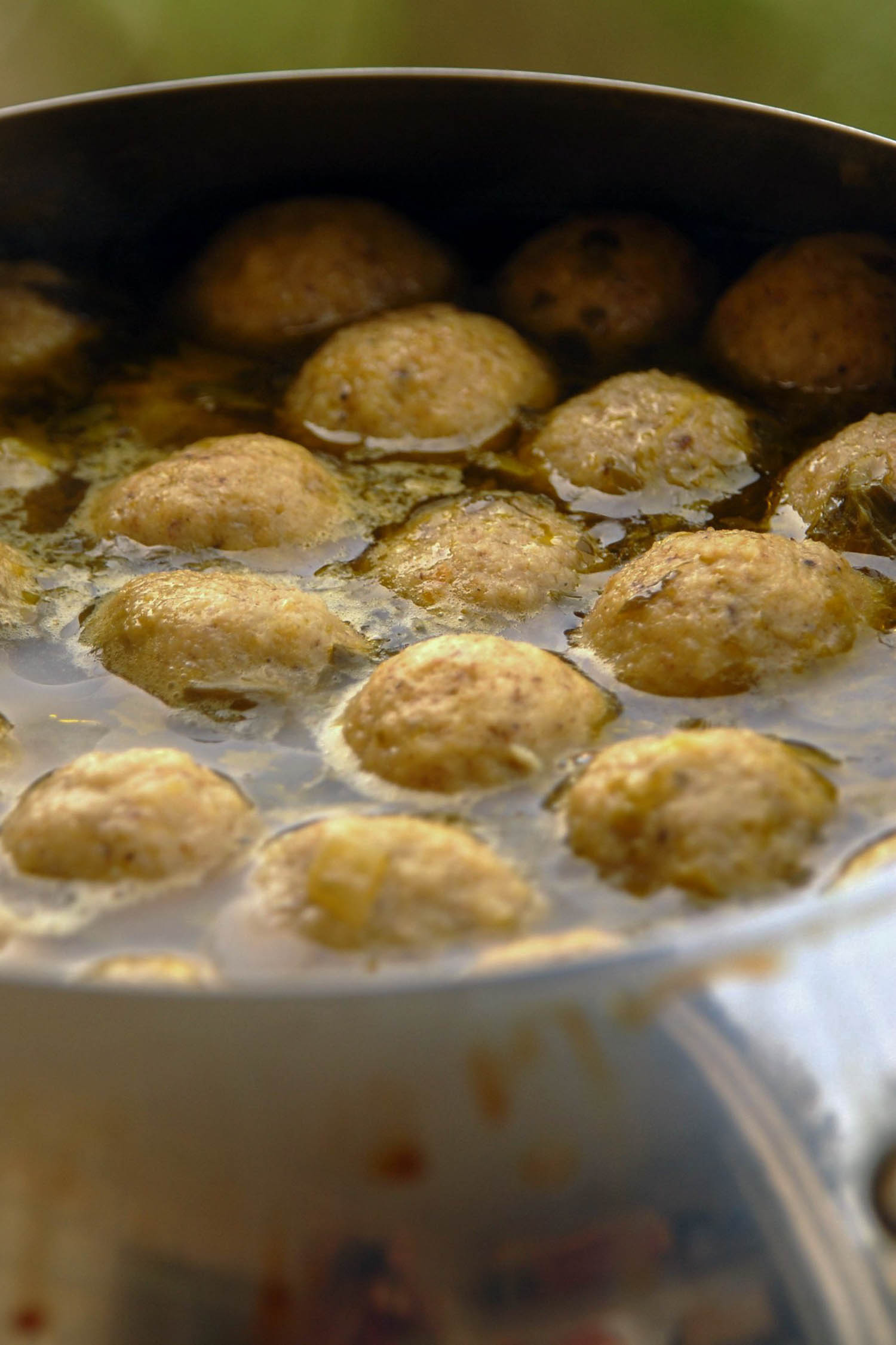 matzah ball soup in a pan simmering, common Rosh Hashanah food